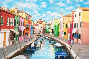 Narrow canal and colorful houses in Burano, Italy.