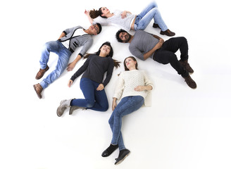 Above view of a happy group of friends lying on white floor.