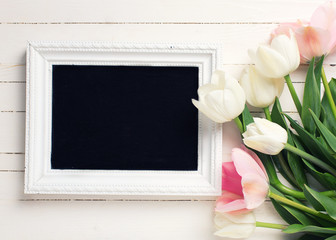 Background with  white and pink tulips and empty blackboard.