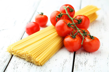 Spaghetti with tomatoes on white wooden background