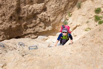 Wall Mural - Young woman climbing desert canyon cliff.