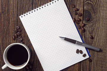 Opened notepad and coffee cup