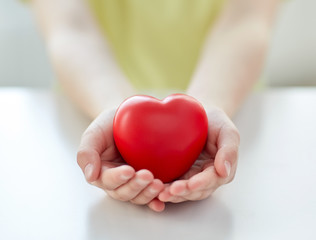 close up of child hands holding red heart
