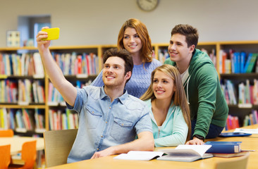 students with smartphone taking selfie at library