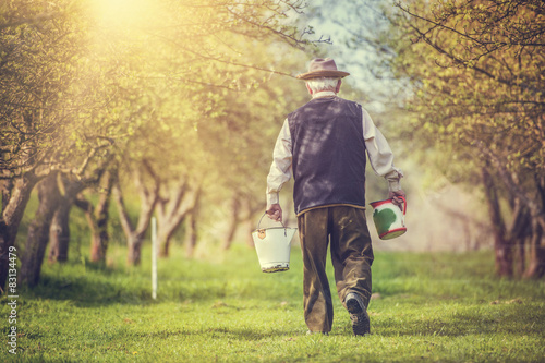 Farmer with jug and bucket for milking outside in green nature