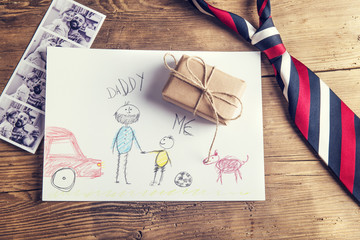 Tie, childs drawing, present and pictures on wooden background