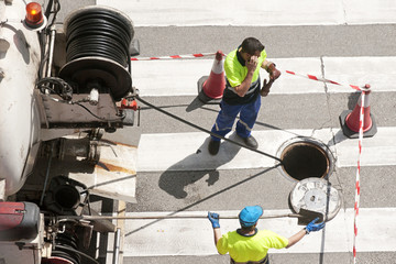 workers moves the manhole cover to check the sewer line