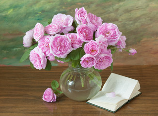 Still life with pink roses bunch and book