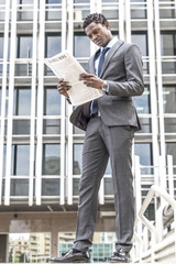 Handsome black businessman reading newspaper outdoor