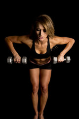 fit woman in black shorts and top weights lean forward