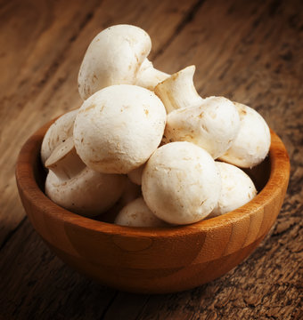 White mushrooms in a bowl on wooden table, selective focus