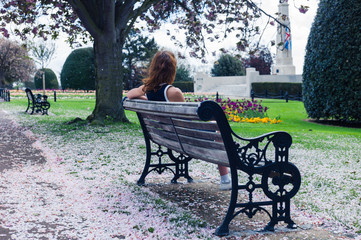 Elegant woman on park bench with cherry blossom