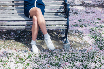 Woman relaxing on bench with cherry blossom