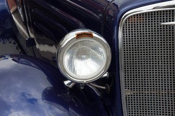A headlight and grill from a classic car.