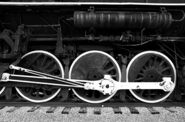 The large white rimmed wheels of an old steam engine.