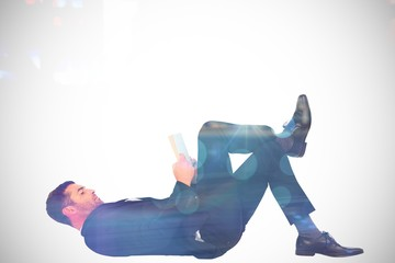 Composite image of businessman lying on the floor reading book