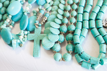 Beads of blue turquoise stone lie on the counter
