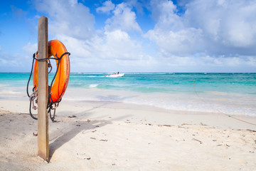 Red round life buoy hanging on wooden pole
