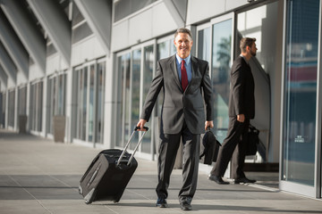 Executive man walks through airport after arriving on flight from business trip with luggage