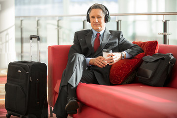 Businessman relaxing at the airport waiting for flight listening to headphones