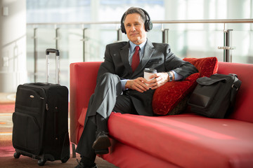 Older executive man calmly sitting at hotel lobby waiting to be taken to flight listening to a meeting
