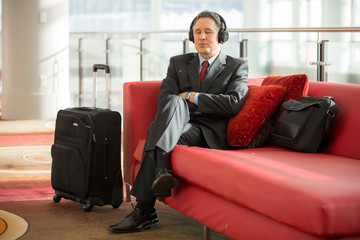 Patient executive business man sits at the train station while traveling on a business trip