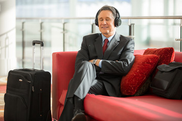 Businessman relaxed and patiently waiting his flight listening to music on headphones