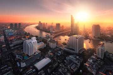 Bangkok city sunlight warm orange,sunrise in morning rooftop view, chao phraya river the office buildings in Bangkok city skyline top view business office in capital city of Thailand Asian