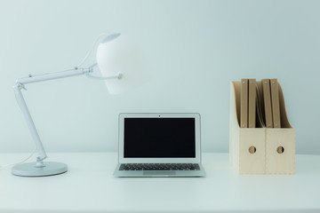 Still-life portrait of computer, pen, coffee mug on table, busin