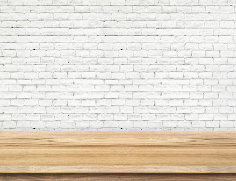 Empty wood table and white brick wall in background. product dis