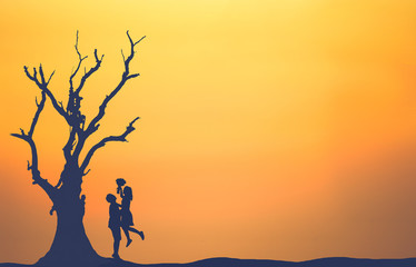 Silhouette of couple in love with tree at sunset.