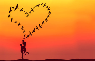 Silhouette of couple in love with heart shaped made by flying bi