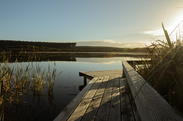 Wooden footpath at the lake in the morning