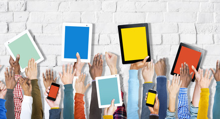 Group of Hands Holding Digital Devices on Brick Wall