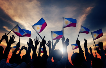 Group of People Waving Philippin Flags Back Lit