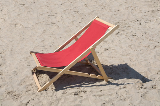 Red lounge chair in wood and fabrics in sand.