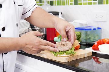 Chef putting beef hamburger on the bun