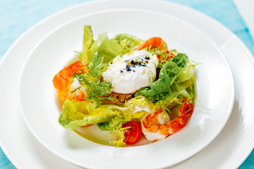 Salad with shrimp and poached egg