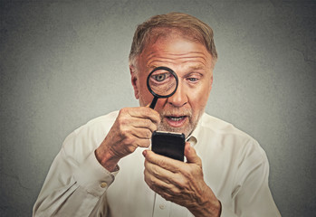 Curious. Senior man looking through magnifying glass smartphone