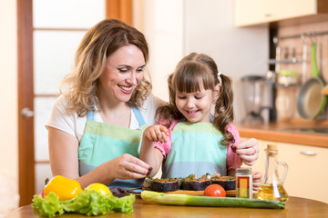 Cute woman with child daughter preparing fish in kitchen