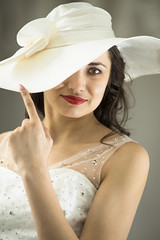 Young woman in white long dress and hat hide one eye.