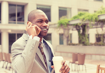 handsome businessman talking on mobile phone drinking coffee