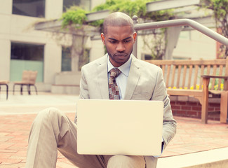 young man surfing web on personal laptop outside