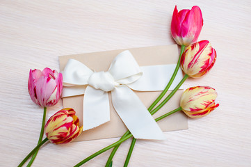 Festive gift box with fresh tulip flowers on white background