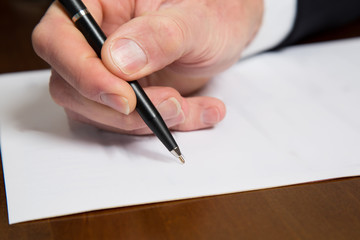 Hand of a businessman holding a pen over a paper