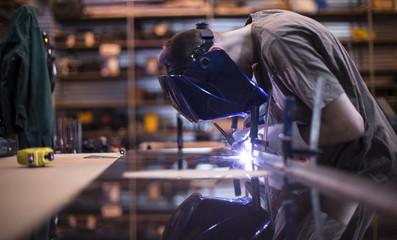 Employee welding stainless steel using welder machine