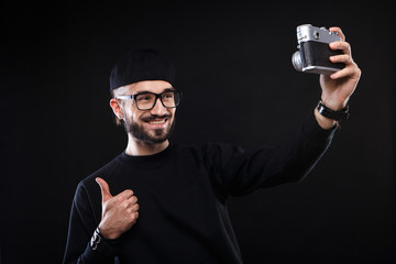 Charismatic guy in sweater , glasses  photo camera