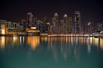 city building at night and water reflect photo