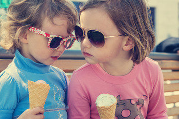 Two little girls eating ice cream.