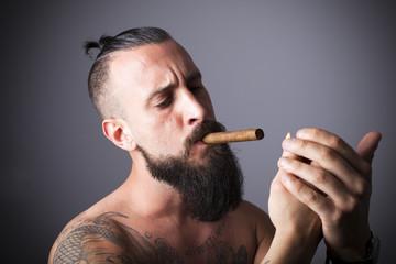 Hombre con barba encendiéndose un cigarro puro